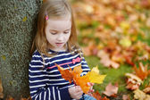 Adorable little girl having fun on autumn day — Stock Photo
