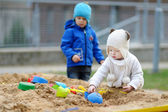 Two kids playing in a sandbox — Stock Photo