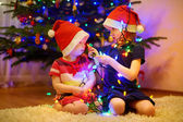 Two sisters decorating Christmas tree — Stok fotoğraf