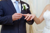 Groom is putting the ring on bride's finger — Stock Photo