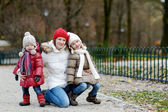 Two sisters and their mom in autumn park — Stock Photo