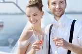 Happy bride and groom drinking champagne — 图库照片