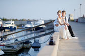 Happy bride and groom sitting on pier — Stockfoto