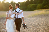 Bride and groom on a beach at sunset — Stock Photo