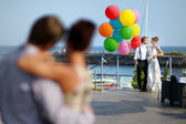 Bride and groom with colorful balloons — Stock Photo