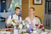Bride and groom at the reception table — Stock Photo