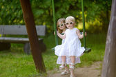 Two sisters having fun on a swing on summer day — Stockfoto
