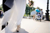 Bride and groom walking across the street — Stock Photo