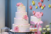 White wedding cake decorated with pink flowers — Stock Photo