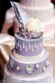Purple wedding cake decorated with flowers — Stock Photo