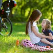 Young mother and her daughter having a picnic — Stock Photo #43481955