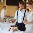Happy bride and groom cutting their wedding cake — Stock Photo