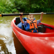 Happy little girl on a kayak on a river — Stock Photo