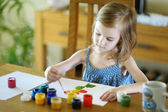 Cute little girl is drawing with paints — Foto Stock