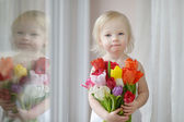 Adorable toddler girl with tulips by the window — Foto de Stock