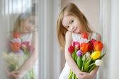 Adorável menina com tulipas pela janela — Fotografia Stock