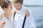 Lyckliga bruden och brudgummen dricker champagne — Stockfoto