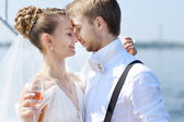 Happy bride and groom drinking champagne — Stockfoto