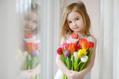 Adorable little girl with tulips by the window — Stock Photo