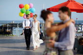 Happy bride and groom with balloons — Stock Photo