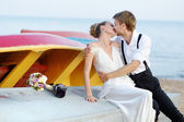 Happy bride and groom hugging by the sea — Stockfoto
