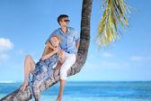 Piękna młoda para siedzi na palmy — Zdjęcie stockowe