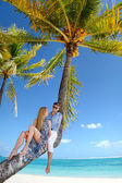 Beautiful young couple sitting on palm tree — Stockfoto