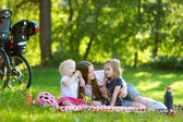 Young mother and her daughters having a picnic — Stock Photo