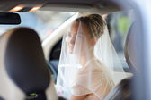 Beautiful young bride portrait in a car — Stock Photo