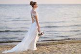 Bride walking along sea coast in wedding dress — Foto Stock