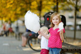 Adorable little girl eating candy-floss outdoors — Stock Photo