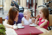 Mother and her daughters relaxing in outdoor cafe — Stock Photo
