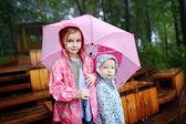 Two sisters under umbrella — Stock Photo