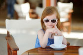 A girl drinking hot chocolate in outdoor cafe — Stok fotoğraf