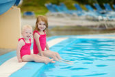Sisters sitting by a swimming pool — Stock Photo