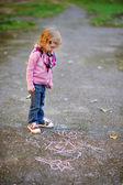 Little girl looking at a chalk drawing — Стоковое фото
