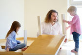Father and daughters assembling table — Stock Photo