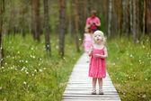 Batole dívka procházky v lese — Stock fotografie