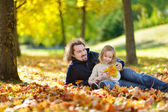 Father and daughter on leaves — Stock Photo