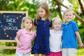 Vier kleine kinderen door schoolbord — Stockfoto