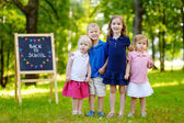 Four little kids by chalkboard — Stock Photo