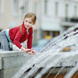 Little girl playing with fountain — Stock Photo #50226629