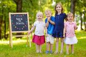 Fyra små barn av svarta tavlan — Stockfoto