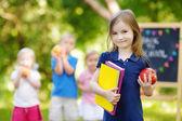 Little schoolgirl going back to school — Stock Photo
