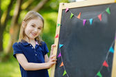 Little schoolgirl by   chalkboard — Stock Photo