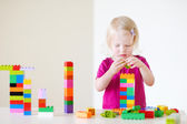 Girl playing with plastic blocks — Stock Photo