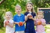 Four little kids by chalkboard — Zdjęcie stockowe