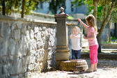 Sisters playing at fountain — Stock Photo