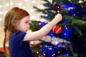 Mała dziewczynka dekorowanie choinki — Zdjęcie stockowe