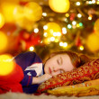 Girl sleeping under Christmas tree — Stock Photo #51716843